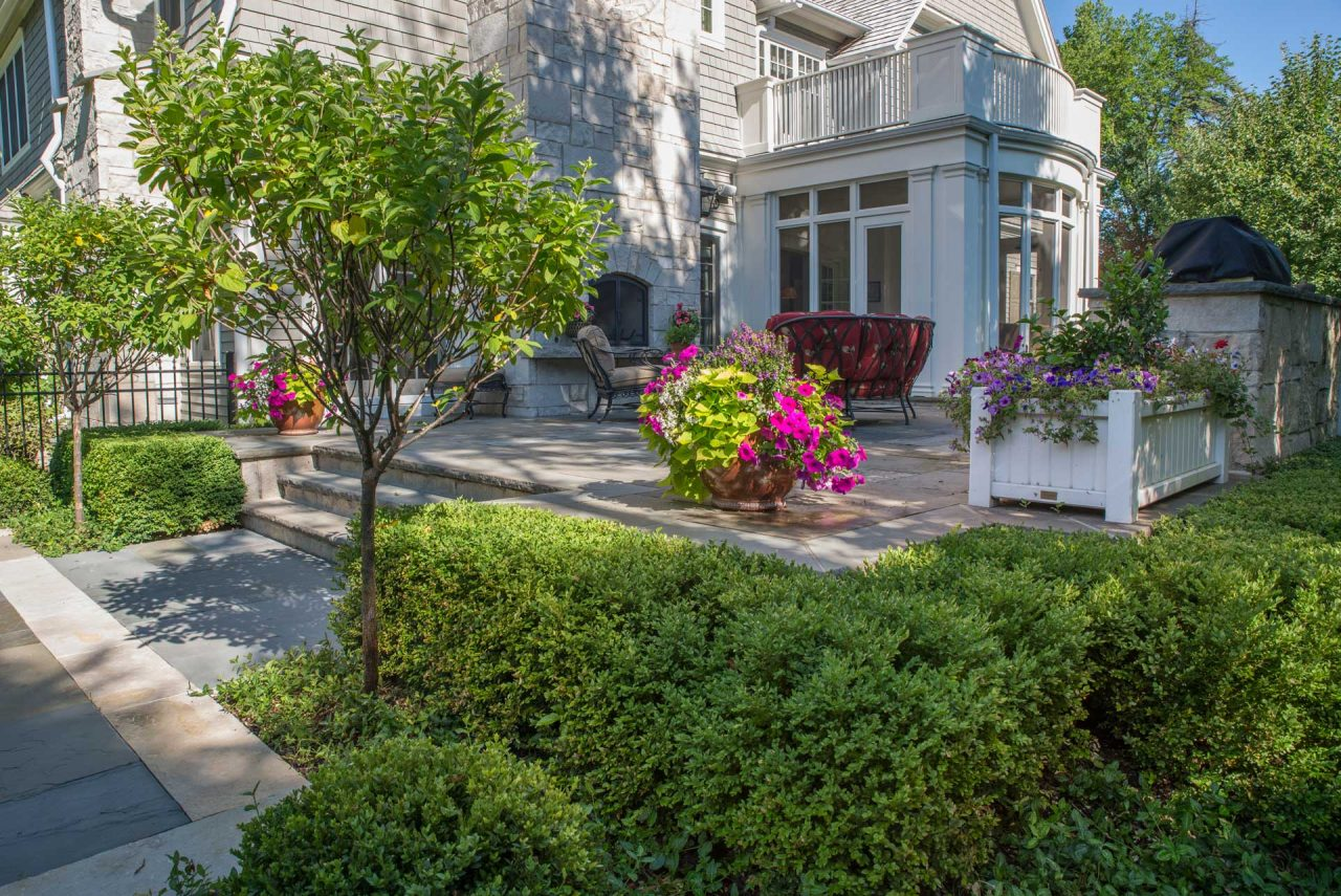 Rear bluestone terrace with outdoor fireplace, kitchen and containers with annual flowers.