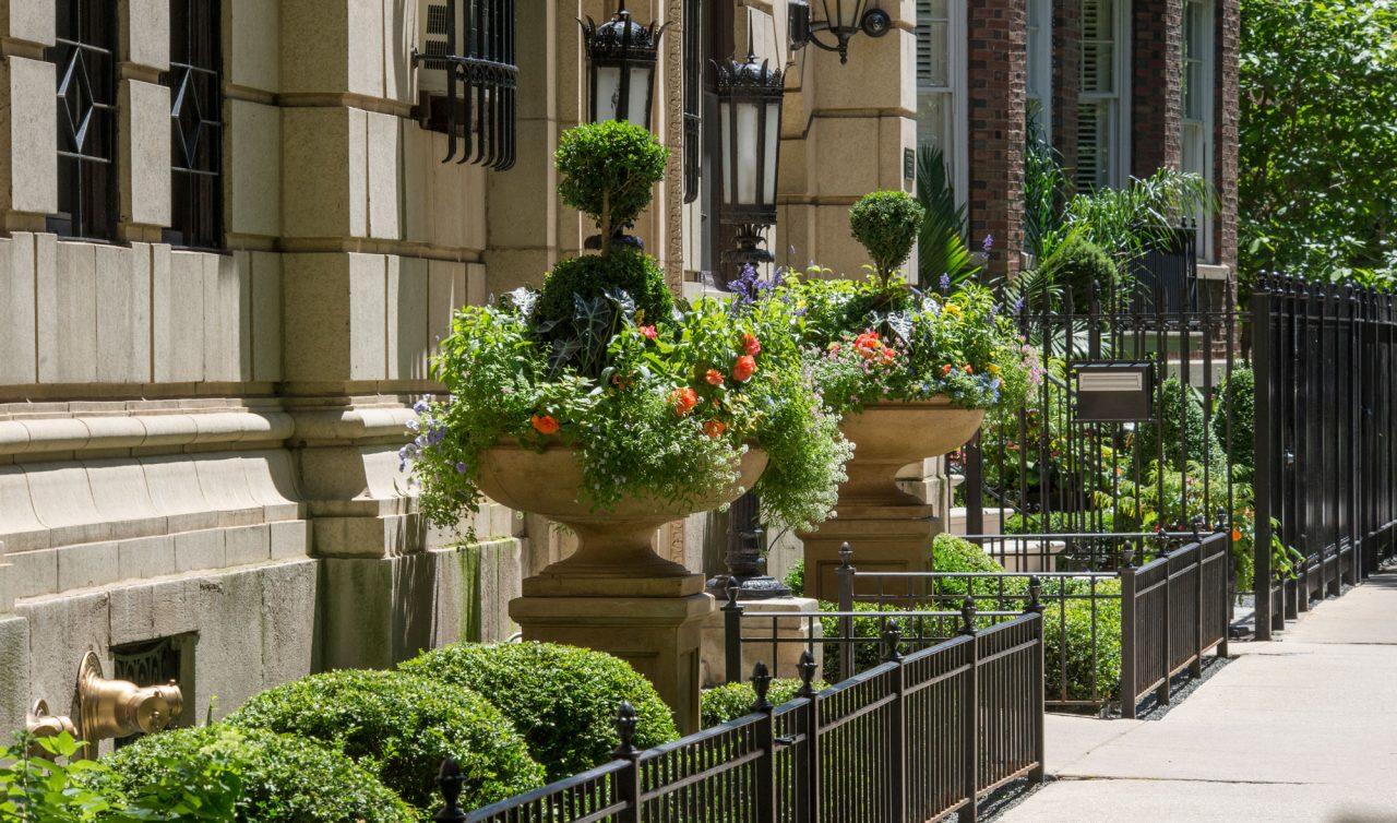 Formal garden behind a low wrought iron fence along a city public sidewalk.