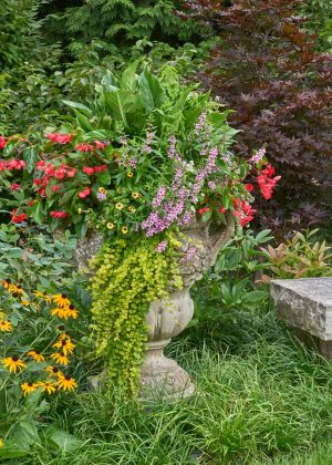 Stone bench and stone urn with annual flowers in the landscape.