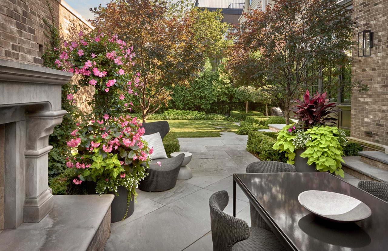 Private city backyard with a outdoor fireplace, dining area on a bluestone patio.