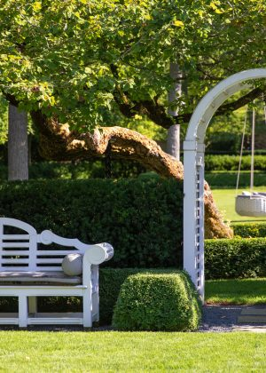 Formal residential garden entrance with a Lutyen's bench, pergola and linear evergreen hedges.