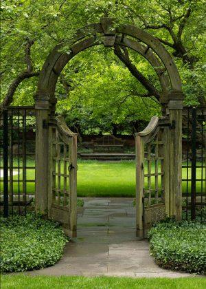 Arched wood arbor with English lattice gates and a bluestone walk.