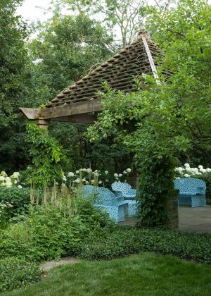 Wood pergola with a peaked roof and bluestone paving set within a garden.