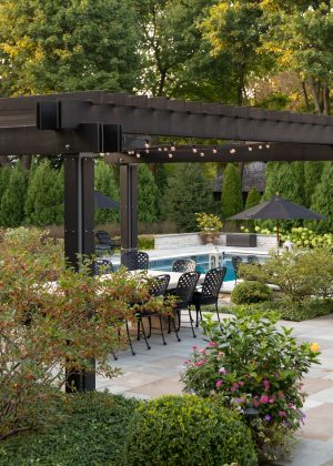Modern wood and steel pergola set within a natural stone terrace overlooking the swimming pool.