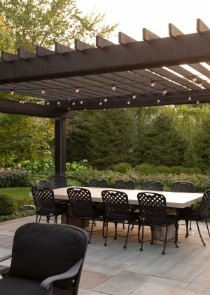 Modern wood and steel pergola with dining table set overlooking the backyard garden.