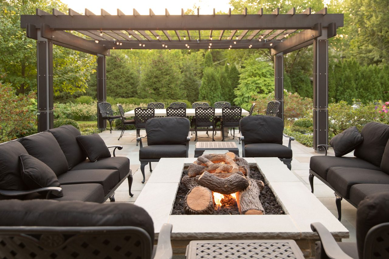 Modern wood and steel pergola with dining table set overlookingModern wood and steel pergola and raised fire pit with faux logs and casual seating. the backyard garden.