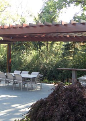 Modern wood and steel pergola with casual dining and a grill center.