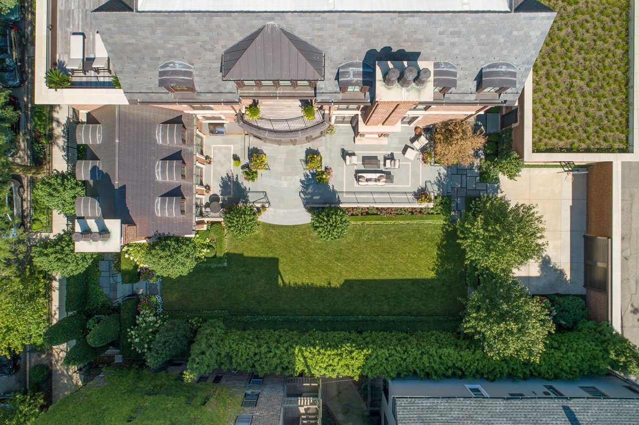 Aerial view overlooking bluestone patio and manicured landscape backyard