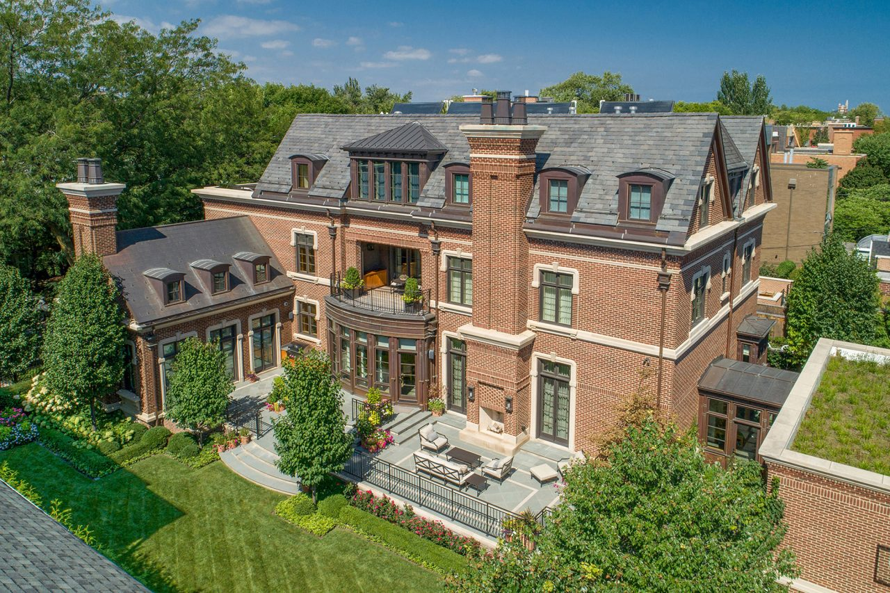 Drone shot of bluestone patio and manicured landscape backyard