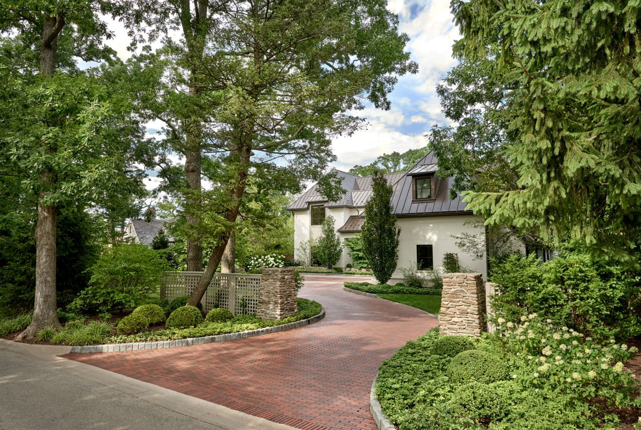 Winding brick driveway surrounded by greenery