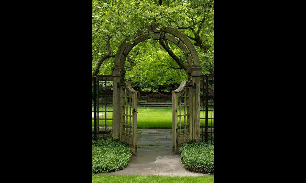 Wooden arched gate with paved walkway