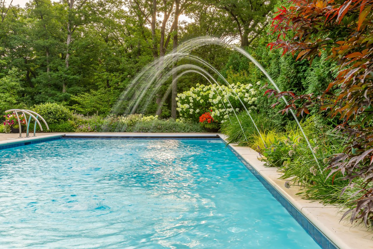 Rectangle pool with water features surrounded by perranual garden