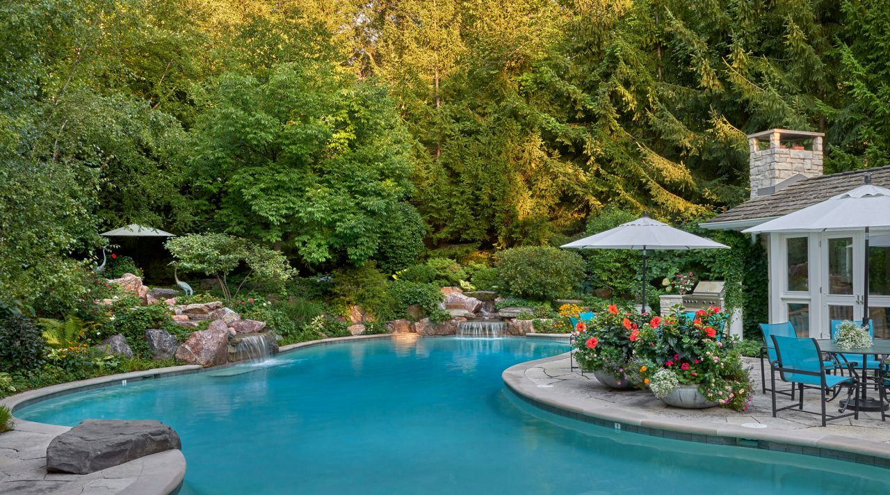 Pool with cascading waterfalls secluded by landscape design