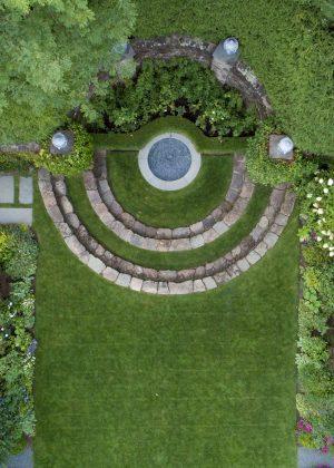 An award winning European influenced symmetrical garden with stone walls and a fountain focal point.