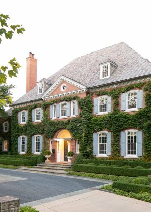 Strong linear boxwood hedges, bluestone curbs and walls forms the formal bluestone paver and gravel driveway.
