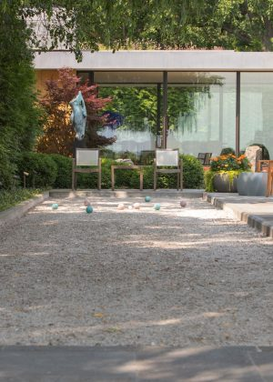 Modern house with private bacci ball court and yard furniture and orange flowers in a round planter.