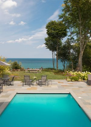 View to Lake Michigan overlooking a turquoise colored pool and bluestone patio.