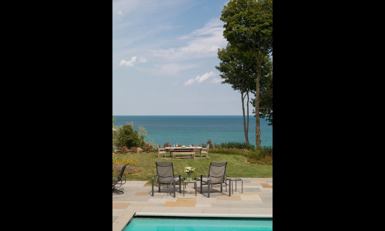 Serene view to Lake Michigan looking over a grass lawn with outdoor dining furniture.