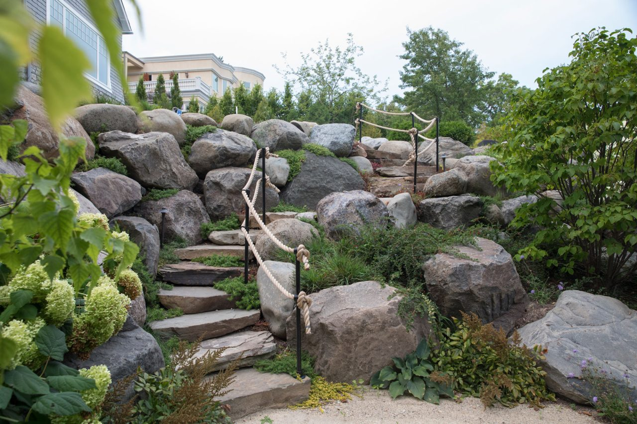 Natural boulder wall with a rope fence and white hydrangea in the foreground.