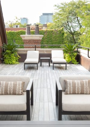 Chicago rooftop garden with flower planters, palm trees, and neutral colored outdoor furniture.