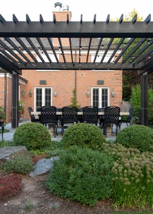 Dark pergola with outdoor dining set viewed from behind boxwoods and a perennial garden.