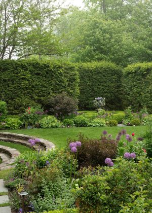 Perennial garden with fountain and lawn surrounded by tall arborvitae privacy hedge.