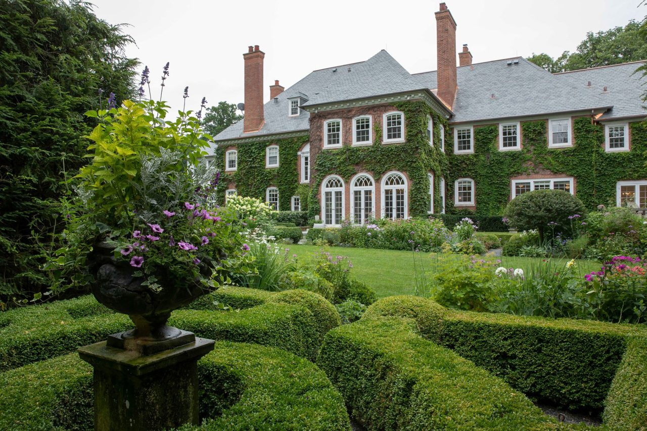 Boxwood parterre garden with flowers in dark, traditional urn, on a large, ivy covered, suburban estate.