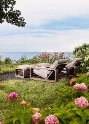 Tranquil lounge area under large maple, surrounded by colorful hydrangeas, with a view of the lake.