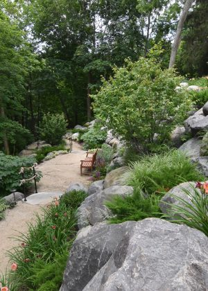 Bluff path with granite boulders, wooden bench, and rope railing