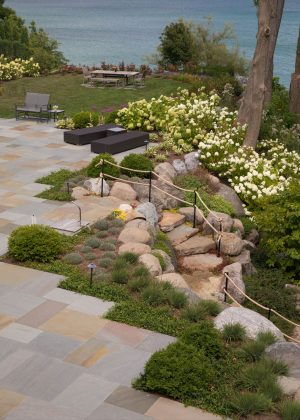 Stone deck overlooking Lake Michigan and bluff with granite boulder steps and rope railing