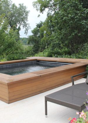 Contemporary rectangle hot tub spa. Cedar planks on hot tub reflect plank pavers