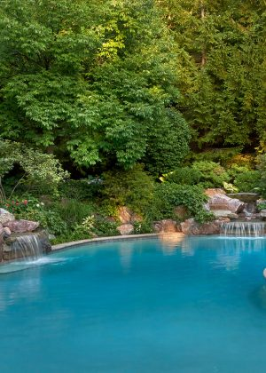 Natural set boulders create spectacular waterfall into poolWaterfall cascading into pool with outdoor seating surrounded with bright annuals