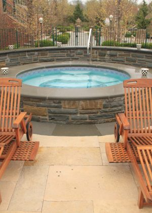 Circular spa with blue stone seat wall
