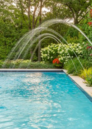 Water jets playfully splash around the pool. Surrounded by perennial garden