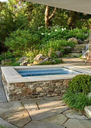 Spa tucked in naturalistic garden setting with lush planting and irregular hardscape.
