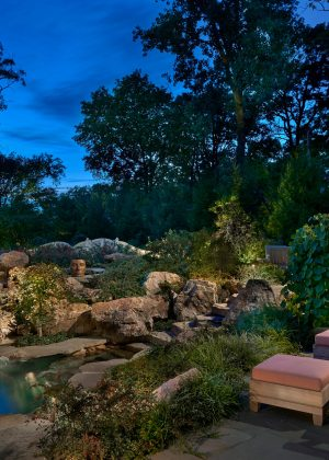 Bluestone pool deck overlooking lighted pool with waterfall at night