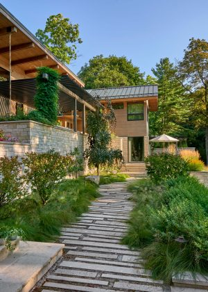 Stone stepper path surrounded by natural plantings, flower beds atop stone wall, and a lofted pergola
