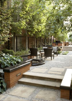 Flagstone steppers embedded in gravel with multiple seating areas and water feature all bordered by a brick and marble wall