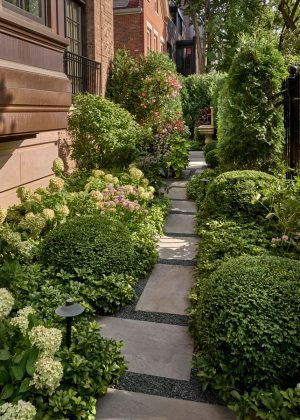 Stepper path through boxwood and perennial flower beds leading to antique fountain