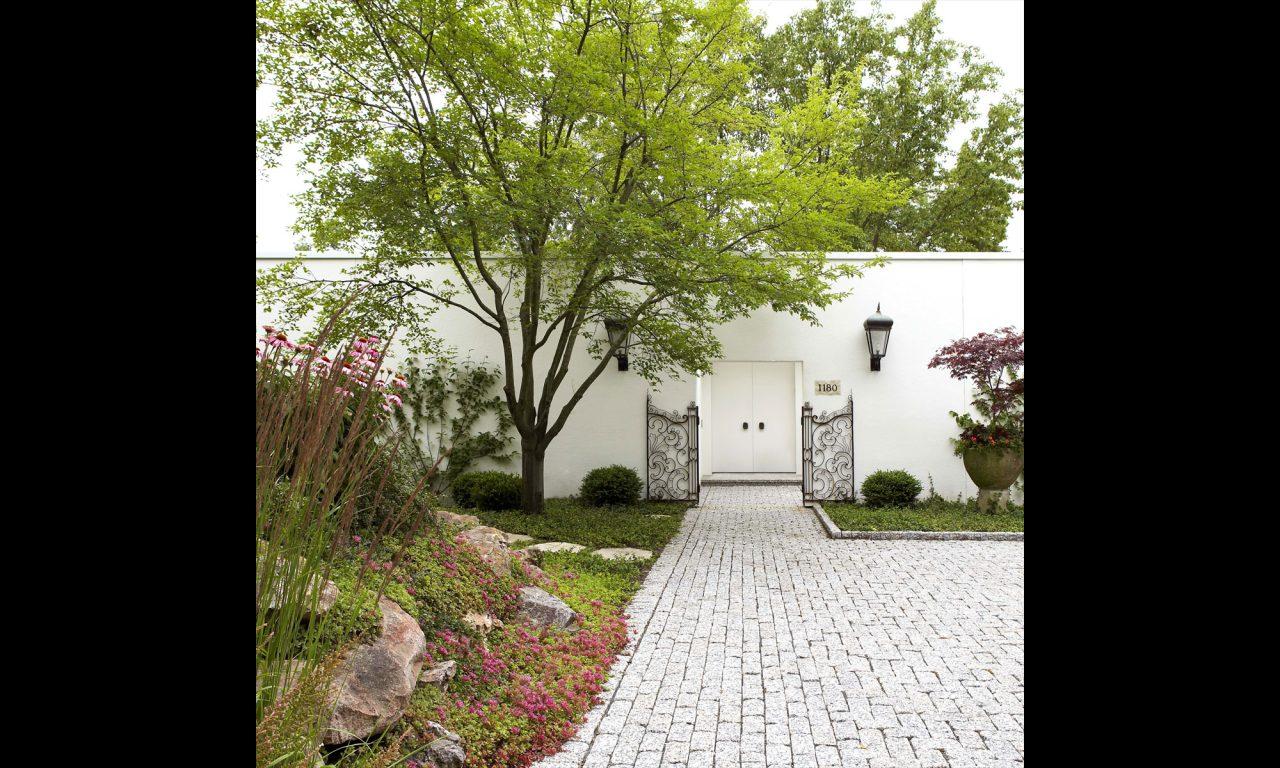 Granit parking area followed by rock garden leading to metal gate