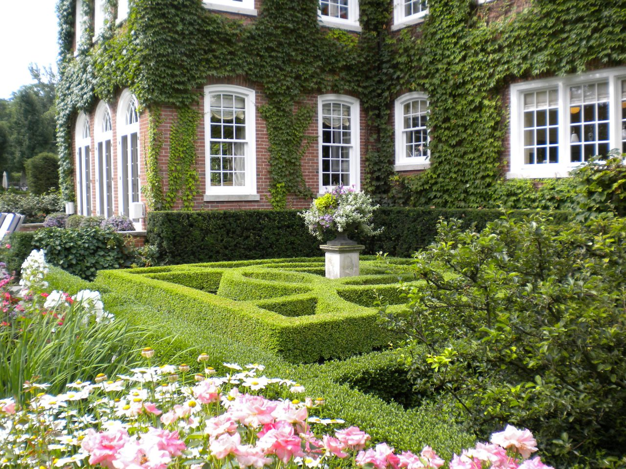Beautiful boxwood parterre in perennial garden with annual container on pedestal