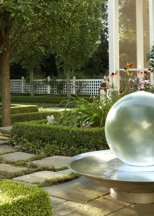 """""""Tranquil garden around Chicagoland with screen porch surrounded by low hedges, flowers, and clear globe fountain on hardscape """""""