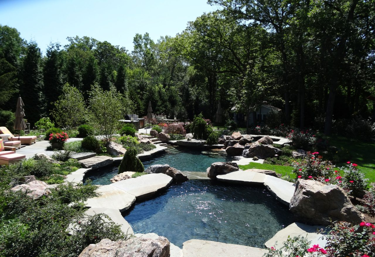 Naturalized dual pool with waterfall and bluestone terrace