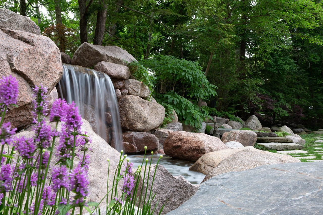 Waterfall surrounded by natural landscape featuring perennials
