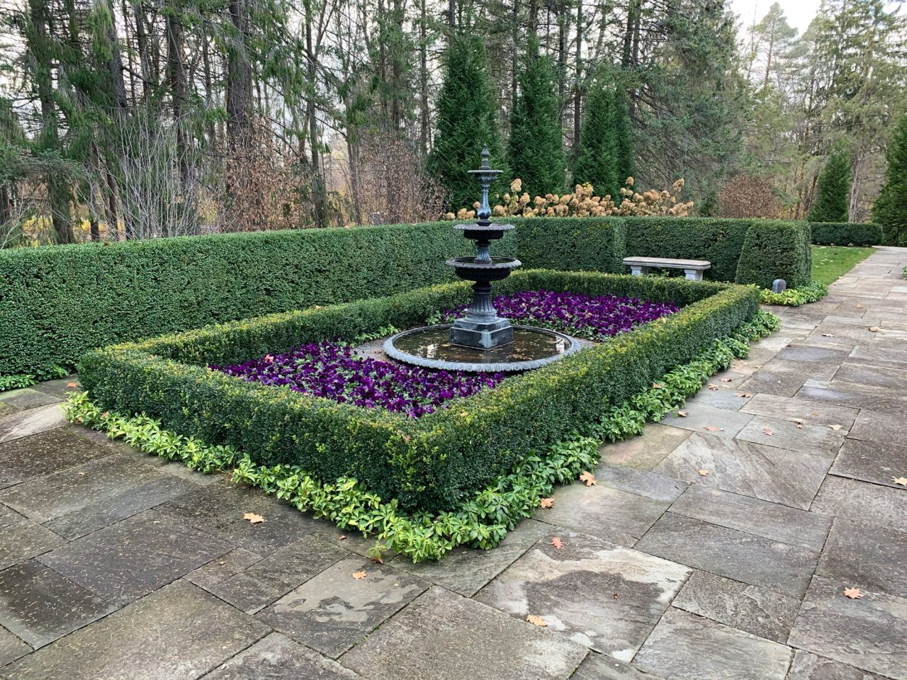Three-tiered fountain surrounded by boxed hedges, annuals, and groundcover