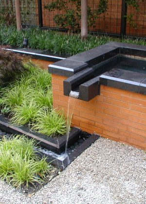 Modern brick and marble trough fountain with Japanese inspired planting