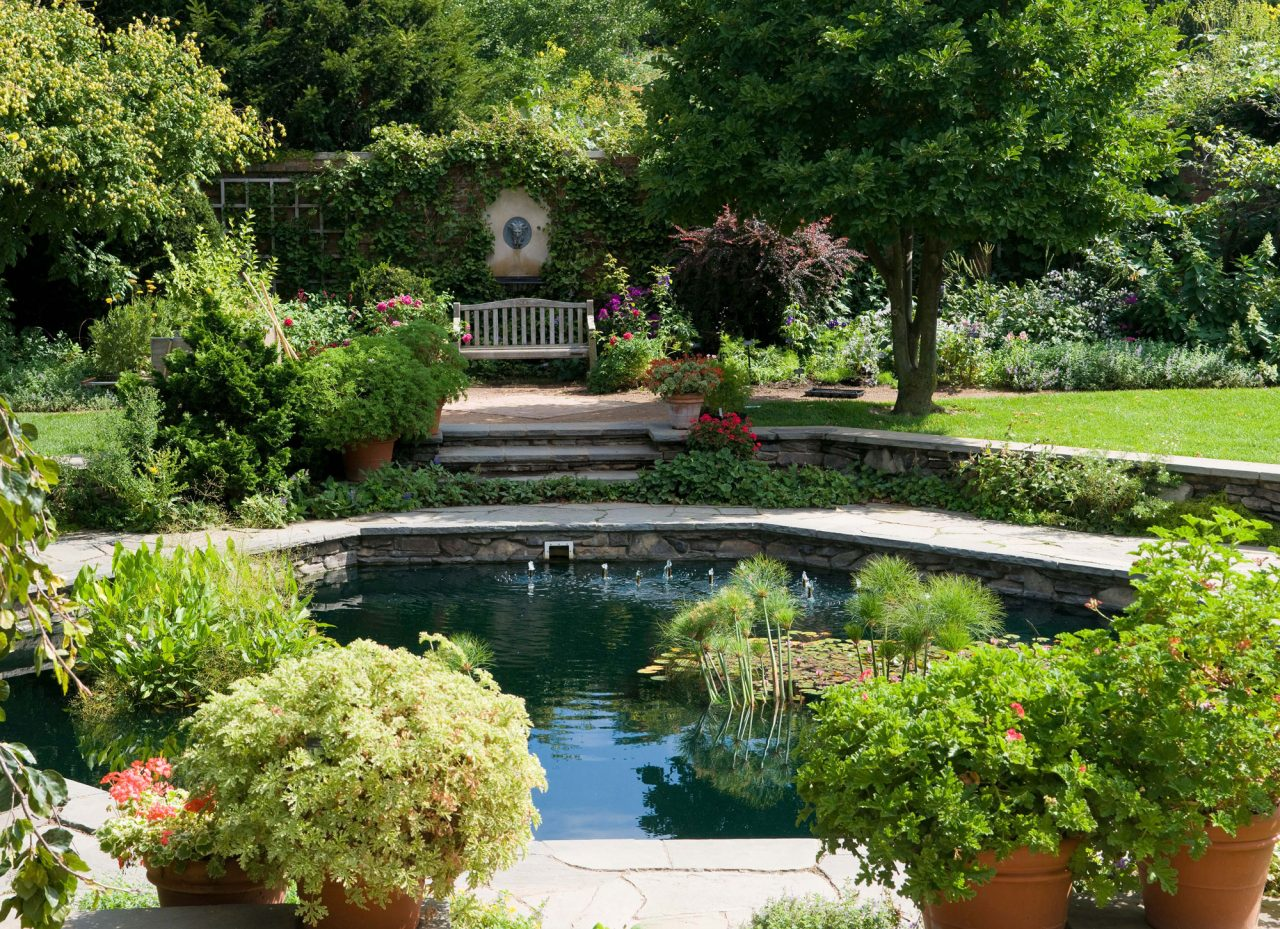 Sunken fountain surrounded by potted plants, flowers, and wooden bench within English Walled Garden at Chicago Botanic Garden