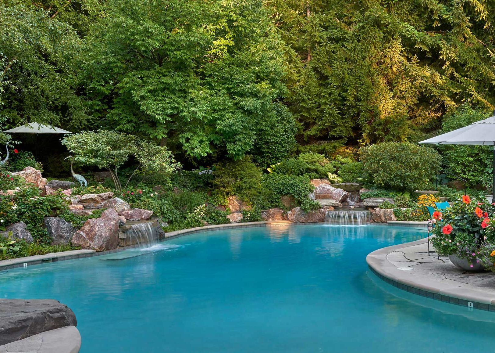 Huge swimming pool with waterfalls, stone deck and large potted plant arrangements by Midwest landscape architect.