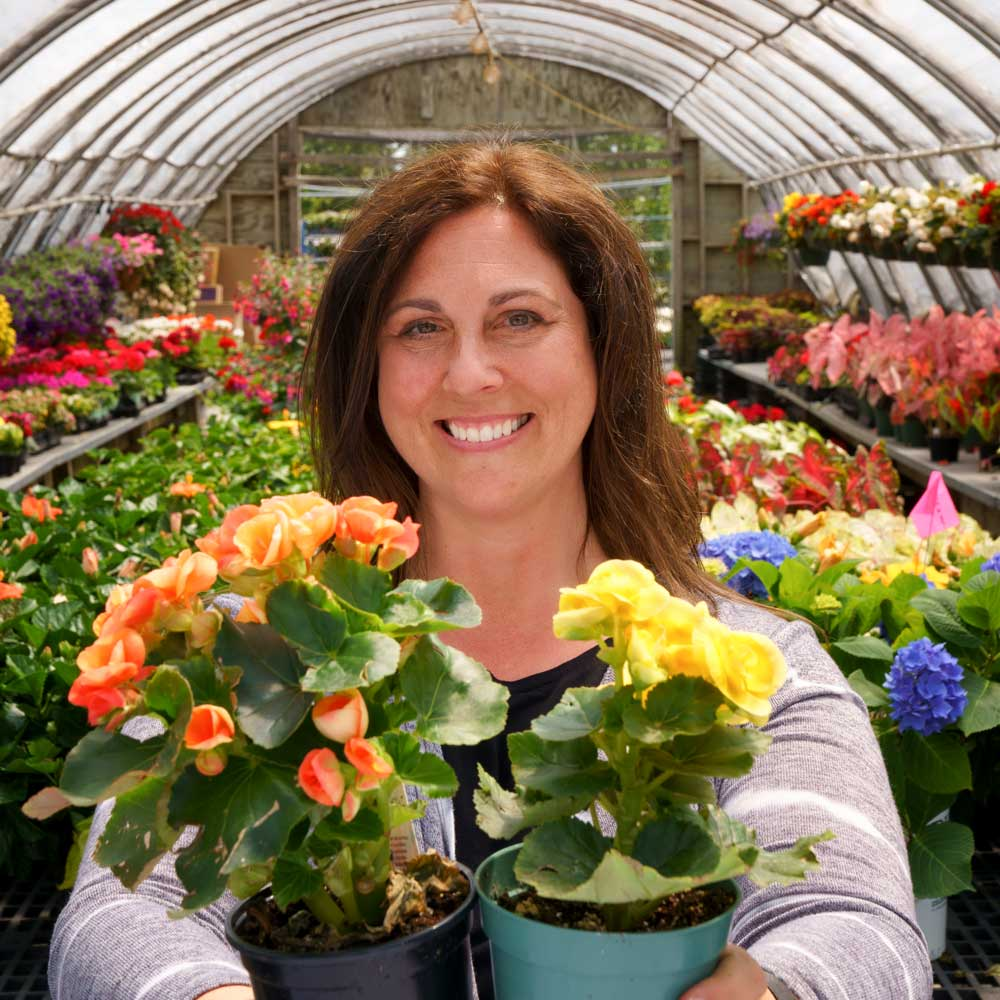 Woman with welcoming smile presents two pots of colorful annuals.